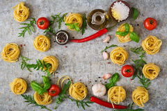 Pasta Tagliatelle nest and ingredients for cooking. (tomatoes, garlic, basil, chili). Top view royalty free stock photos