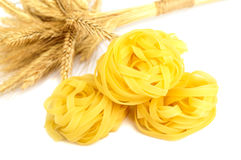 Pasta tagliatelle in a nest and spikelets wheat isolated on white background Stock Image