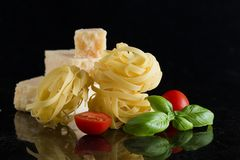 Pasta Tagliatelle, parmesan arranged on marble table. Delicious dry uncooked ingredients for traditional Italian cuisine Royalty Free Stock Images
