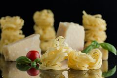Pasta Tagliatelle, parmesan arranged on marble table. Delicious dry uncooked ingredients for traditional Italian cuisine Stock Image