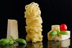 Pasta Tagliatelle, parmesan arranged on marble table. Delicious dry uncooked ingredients for traditional Italian cuisine Stock Photos