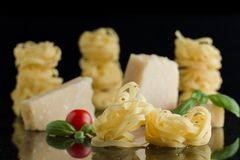 Pasta Tagliatelle, parmesan arranged on marble table. Delicious dry uncooked ingredients for traditional Italian cuisine Royalty Free Stock Photo