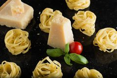 Pasta Tagliatelle, parmesan arranged on marble table. Delicious dry uncooked ingredients for traditional Italian cuisine Royalty Free Stock Photos