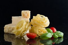 Pasta Tagliatelle, parmesan arranged on marble table. Delicious dry uncooked ingredients for traditional Italian cuisine Stock Photography