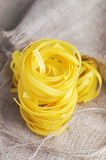 Pasta tagliatelle on the sacking background Royalty Free Stock Images