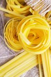Pasta tagliatelle on the sacking background Stock Images