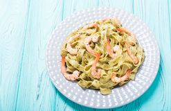 Pasta tagliatelle with sauce pesto and shrimps Italian food background. Pasta tagliatelle with sauce pesto and shrimps . Italian food background stock photo