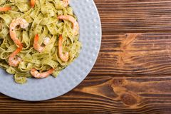 Pasta tagliatelle with sauce pesto and shrimps Italian food background. Pasta tagliatelle with sauce pesto and shrimps . Italian food background stock photography
