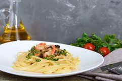 Pasta tagliatelle with seafood and cream sauce on a white plate on a wooden table.  Stock Images