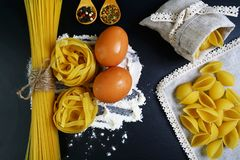 Pasta tagliatelle, spaghetti, italian foods concept and menu design, spices on wooden spoons, shells in a bag, raw eggs and flour royalty free stock image