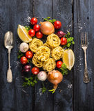 Pasta tagliatelle with tomatoes, vegetables and spices for tomato sauce,spoon and fork Royalty Free Stock Image