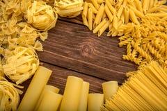 Pasta temat Różni rodzaje makaron na drewnianym tle Farfalle, fettuccine, klusek, fusilli i penne rigate, zdjęcie stock