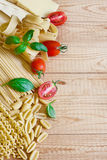 Pasta, tomato and basil bacground. Mix of pasta, tomato, basil and parmigiano. Copy space background Royalty Free Stock Image
