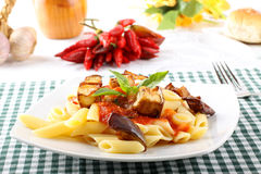 Pasta with tomato, basil and eggplant. On complex background royalty free stock photo