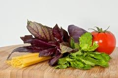 Pasta, tomato, basil, mint on wood board. Italian pasta, fresh tomato, basil, mint on wood board Stock Photography