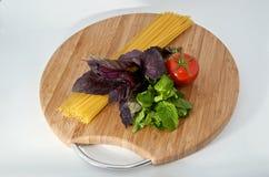 Pasta, tomato, basil, mint on wood board. Italian pasta, fresh tomato, basil, mint on wood board Royalty Free Stock Photo