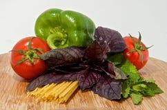 Pasta, tomato, basil, mint on wood board. Italian pasta, fresh tomato, basil, mint on wood board Royalty Free Stock Image