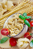 Pasta, tomato and basil. Mix of pasta, tomato, basil and parmigiano. Selective focus Royalty Free Stock Photo