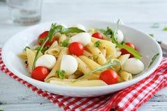 Pasta with tomato and mozzarella slices in a bowl on napkin Royalty Free Stock Photos