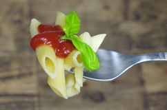 Pasta with tomato sauce and basil on fork Royalty Free Stock Photos