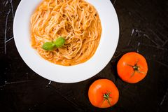 Pasta in tomato sauce on a black background stock image