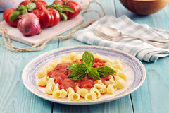 Pasta with tomato sauce. Pasta conchiglie type with tomato sauce on an aqamarine wooden table surrounded by fresh tomatoes and onion Royalty Free Stock Image