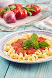 Pasta with tomato sauce. Pasta conchiglie type with tomato sauce on an aqamarine wooden table surrounded by fresh tomatoes and onion Stock Images