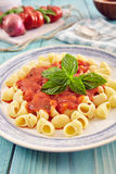 Pasta with tomato sauce. Pasta conchiglie type with tomato sauce on an aqamarine wooden table surrounded by fresh tomatoes and onion Royalty Free Stock Photography