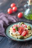 Pasta with tomato sauce, olives and capers on the plate. On the wooden table Stock Photos