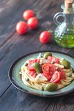 Pasta with tomato sauce, olives and capers on the plate. On the wooden table Stock Image