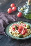 Pasta with tomato sauce, olives and capers on the plate. On the wooden table Royalty Free Stock Photography
