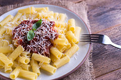 Pasta with tomato sauce and parmigiano on natural wooden table. Stock Image