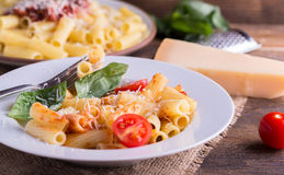 Pasta with tomato sauce and parmigiano on natural wooden table. Stock Photos