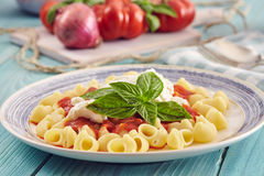 Pasta with tomato sauce and ricotta. Pasta conchiglie type with tomato sauce and ricotta on an aquamarine wooden table surrounded by fresh tomatoes and onion Royalty Free Stock Photo