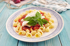 Pasta with tomato sauce and ricotta. Pasta conchiglie type with tomato sauce and ricotta on an aquamarine wooden table surrounded by fresh tomatoes and onion Stock Photography