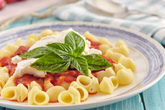 Pasta with tomato sauce and ricotta. Pasta conchiglie type with tomato sauce and ricotta on an aquamarine wooden table surrounded by fresh tomatoes and onion Royalty Free Stock Photos