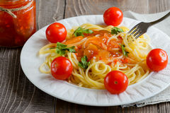 Pasta in tomato sauce with tomatoes and greens. On a wooden background Stock Images