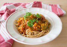 Pasta with tomato sauce, white plate wooden table. Pasta with tomato sauce, parsley and brussels sprouts on a white plate against of wooden table and red white Stock Photo