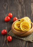 Pasta with tomato on a wooden background. Nest pasta with tomatoes on a wooden background Stock Photography