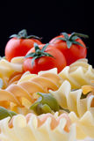 Pasta and Tomatoes. Colorful Dry Italian Pasta On Black Background. Focus on pasta Royalty Free Stock Image