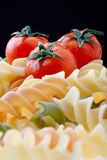 Pasta and Tomatoes. Colorful Dry Italian Pasta On Black Background. Focus on tomatoes Royalty Free Stock Images