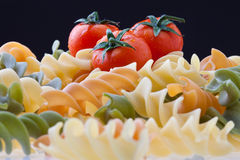 Pasta and Tomatoes. Colorful Dry Italian Pasta On Black Background. Focus on tomatoes Royalty Free Stock Image