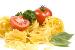 Pasta and tomatoes. Some tomatoes on a pile of pasta royalty free stock images