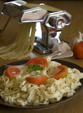 Pasta with tomatoes. Homemade fettuccine pasta with tomatoes and pasta machine in the background stock photos