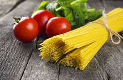 Pasta, tomatoes, basil on a dark wooden background Royalty Free Stock Photos