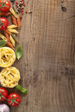 Pasta tomatoes basil frame on wooden background Royalty Free Stock Images