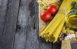 Pasta, tomatoes, basil, olive oil on a dark wooden background Stock Image
