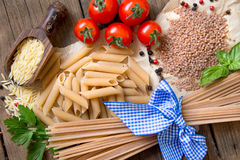 Pasta, tomatoes, basil and parsley on wooden background Royalty Free Stock Photos