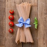 Pasta, tomatoes and basil on wooden background Stock Image