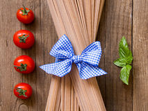 Pasta, tomatoes and basil on wooden background Stock Images